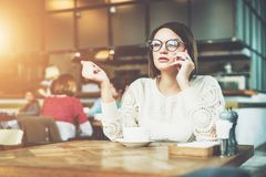 Young serious businesswoman in glasses sitting in cafe at wooden table and talking on cell phone. Telephone conversations. Hipster girl freelancer discusses Stock Photography