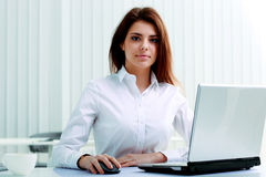 Young serious businesswoman sitting at the table with laptop Royalty Free Stock Photography