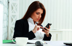 Young Serious Businesswoman Typing On Her Smartphone Stock Photography