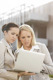 Young serious businesswomen working on laptop while standing against office building Stock Photos
