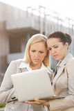 Young serious businesswomen working on laptop while standing against office building Royalty Free Stock Photos