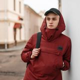 Young serious confident man in a red stylish long jacket with a hood in a black fashionable cap with a trendy sports backpack. Poses on the street near the royalty free stock photos