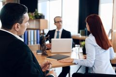 Young serious couple consults, sitting in office of divorce advocate. Adult couple is divorced. Dissolution of marriage of two adults. Divorce of adult couple Stock Photos