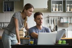 Young serious couple discussing domestic bills with papers and l royalty free stock images