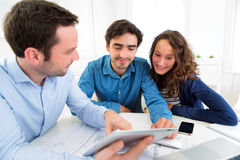 Young serious couple meeting a real estate agent. View of a young serious couple meeting a real estate agent royalty free stock images