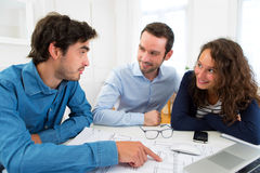 Young serious couple meeting a real estate agent. View of a young serious couple meeting a real estate agent royalty free stock image