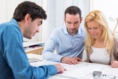 Young serious couple meeting a real estate agent. View of a young serious couple meeting a real estate agent royalty free stock photo