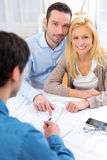 Young serious couple meeting a real estate agent. View of a young serious couple meeting a real estate agent stock images