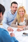 Young serious couple meeting a real estate agent. View of a young serious couple meeting a real estate agent stock photo