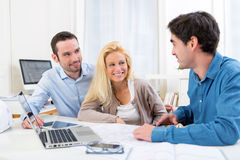 Young serious couple meeting a real estate agent. View of a young serious couple meeting a real estate agent royalty free stock photography