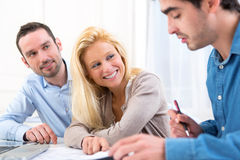 Young serious couple meeting a real estate agent. View of a young serious couple meeting a real estate agent stock photos