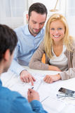 Young serious couple meeting a real estate agent. View of a young serious couple meeting a real estate agent stock image