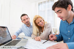 Young serious couple meeting a real estate agent. View of a young serious couple meeting a real estate agent stock photography
