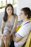 Young serious couple sitting on bench Stock Images