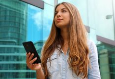 Young serious and determined business woman standing in front of modern building with phone in her hand stock photo