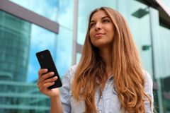 Young serious and determined business woman standing in front of modern building with phone in her hand stock photography