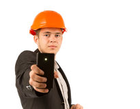 Young Serious Engineer Holding Black Mobile Phone. Solo Young Serious Male Engineer in Orange Helmet Holding Modern Black Mobile Phone. Looking at Camera Stock Photography