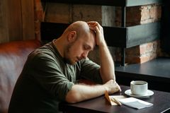 Young serious fashionable man sitting alone in loft-styled cafe stock photos