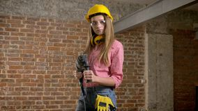 Young serious girl builder is holding drill in her hands, turning on, building conception.  stock footage