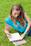 Young serious girl lying on the grass in a park Stock Image