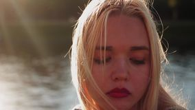 Young serious girl posing on the gren grass near the river at sunset stock video footage