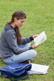 Young serious girl reading a book while sitting Stock Photography
