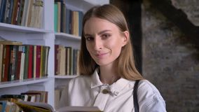 Young serious girl is reading book, watching at camera, library on background.  stock video