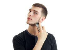 Young serious guy in the black shirt shaves his beard. Is  on a white background Royalty Free Stock Photos