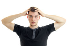 Young serious guy kept his hands behind his head and looks directly isolated on a white background Royalty Free Stock Image