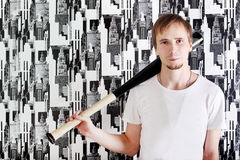 Young serious man with beard in shirt stands with bat Royalty Free Stock Image