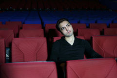 Young serious man in black watches movie Stock Images