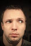 Young serious man cautiously looking away Stock Photos