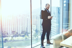 Young serious man CEO in suit is ordering on-line car for business trip via cell telephone. Male is standing in conference room against window with view of Hong Stock Photography