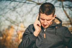 Young serious man holding mobile phone, using smartphone, making a call, talking on the phone, standing on sunny street.  Stock Photos