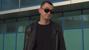 Young serious man in leather jacket and sunglasses does not accept offer by shaking head outdoor.  stock video footage