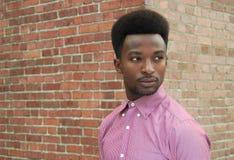 Young serious man profile portrait brick wall pink shirt stock photos