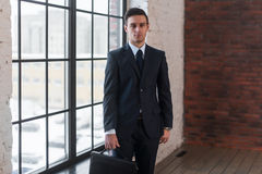 Young serious man standing near office window. Manager director boss entrepreneur employer. Royalty Free Stock Images