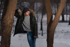 Young serious man stands near the tree in the winter park Stock Photo