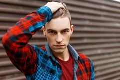 Young serious man with a stylish hairstyle in a trendy t-shirt in a fashionable plaid shirt poses near a vintage metal wall. On a summer day. Stylish handsome stock image