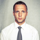 Young serious man in white shirt with tie. Over gray background. Closeup square studio portrait with vintage tonal correction old style photo filter royalty free stock photo