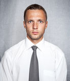 Young serious man. In white shirt with tie over gray background. Studio portrait Royalty Free Stock Images