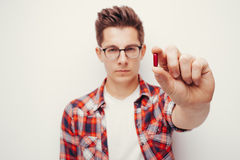 Young serious men in red shirt holding some pill hand. Young serious man in red shirt holding some pill hand. Isolated stock photo