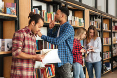 Young serious men students standing in library reading books. Image of young serious men students standing in library reading books. Looking aside royalty free stock photography