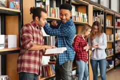 Young serious men students standing in library reading books. Image of young serious men students standing in library reading books. Looking aside stock image
