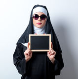 Young serious nun with board. On white background Royalty Free Stock Photography