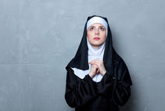 Young serious nun. On grey background stock photos