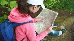Young serious tourist woman with backpack looking to her map and lifting up eyes checking with local terrain stock video footage