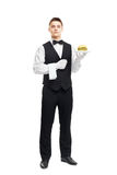 Young serious waiter holding hamburger on plate. Full length portrait of young serious waiter holding hamburger on plate isolated on white background royalty free stock photography