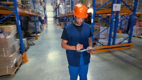 A young serious warehouse inspector works at a storage facility. stock video