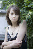 Young serious woman. Standing at bush royalty free stock images